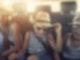 Drei Kinder mit Hüten und Sonnenbrillen sitzen auf der Rückbank eines Autos und lachen sich kaputt.
