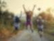 Kinder hüpfen auf dem Feldweg bei Sonnenuntergang.