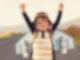 Ein kleiner Junge hat einen selbst gebastelten Flieger auf dem Rücken und reißt die Arme hoch.