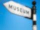 """Ein schwarz weißes Schild auf dem """"Museum"""" drauf steht."""