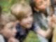 Kinder untersuchen einen Baum mit einer Lupe.