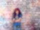 Ein Junge steht mit verschränkten Armen vor einer mit bunter Farbe versehenen Steinwand. Er trägt eine lila-schwarze Langhaarperücke, verschränkt die Arme und guckt in die Kamera. Über ihm, an der Wand, steht #i like foto.