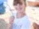 Ein Mädchen sitzt an einem Tisch mit Schminkutensilien, hält einen Pinsel in der rechten Hand und lächelt in die Kamera.