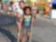 Zwei kleine Mädchen stehen gemeinsam auf einem Tretroller und versuchen damit zu fahren.