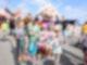 Fünf kleine Kinder stehen vor einem Maskottchen in einem Schafskostüm. Alle Kinder halten eine Autgrammkarte des Maskottchen in der Hand und lächeln in die Kamera.