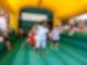 Das innere einer Hüpfburg. Mehrere kleine Kinder hüpfen auf einer mit Luft befüllten, grünen Fläche. Auf dem Rand der Hüpfburg sitzen, auf beiden Seiten, Kinder und gucken zu. Die Hüpfburg hat ein gelbes Dach.