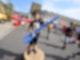 Ein kleiner Junge steht auf einer runden Holzplatte. In der Hand hält er einen blauen, langen Stab aus Styropor, der an einem Ende zu einer Öse geformt ist. Der Junge lächelt in die Kamera.