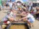Mehrere Wasserbecken sind hintereinander angeordnet und mit Wasser gefüllt. Auf beiden Seiten der Bassins sitzen Kinder die mit Frisbees Sand vom Grund der Behälter sammeln und auf etwas untersuchen.