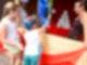 An einem Dosenwurfstand stehen nebeneinander ein junges Mädchen und ein kleiner Junge. Der Junge wirft gerade einen Ball auf einen Dosenstapel. Rechts daneben steht eine Verkäuferin und schaut zu.