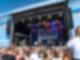 Eine Menschenmenge steht vor einer großen Bühne auf der gerade eine Band spielt und eine Frau in ein Mikrofon singt.