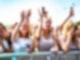 Mehrere junge Frauen stehen an einem Absperrgitter. Einige von ihnen heben die Hände in die Luft.Zwei von ihnen halten Smartphones hoch um ein Foto zu machen.