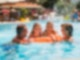 Zwei Mädchen liegen auf einer großen, orangenen, durchsichtigen Luftmatratze im Schwimmbecken von einem Freibad und gucken in die Kamera. Rechts daneben ist eine Frau, links ein Mann - beide lachen die Kinder an und halten sich an der Matratze fest.