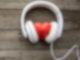 Ein weißer Kopfhörer liegt auf einer Fläche aus dunklen Holzplanken. Die Hörmuscheln umschließen ein rotes Herz aus Stein.