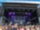 Viele Menschen stehen vor einer großen Bühne auf der gerade eine Band spielt.