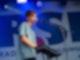 Ein Sänger stehe auf einer Bühne und singt in ein Mikrofon. Dabei spielt er gleichzeitig auf einem Keyboard das vor im aufgebaut ist.