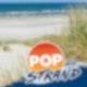 An einem Strand steht ein Holzpfahl an dem vier Schilder befestigt sind. Auf jedem der Schilder steht ein Künstlername. Von oben nach unten: Wincent Weiss, Lena, Namika, Special Guest.
