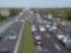 Blick aus der Vogelperspektive auf eine Autobahn. Auf der rechten Seite bilden Autos eine Rettungsgasse durch die ein Rettungswagen mit Blaulicht fährt.