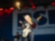 Eine Frau steht auf einer Bühne. Sie hat eine EGitarre vor sich umgebunden und singt in ein Mikrofon.