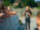 Eine junge Frau rennt in Richtung Kamera und singt dabei in ein Mikrofon. Links neben ihr ist eine Menschenmenge die hinter einer Absperrung steht und ihr die Hände entgegen streckt.