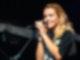 Eine Frau schaut in die Kamera und singt in ein Mikrofon