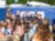 Mehrere Menschen stehen vor zwei Personen die gemeinsam ein Foto machen.