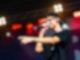 Ein junger Mann steht rechts im Bild, mit Blick nach links. Er singt in ein Mikrofon. Der linke Arm ist gestreckt, mit dem Zeigefinger zeigt er nach vorne.