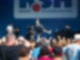 Eine Menschenmenge steht vor einer Bühne auf der eine Band steht. Ein junger Mann singt in ein Mikrofon und hebt dabei sein rechtes Bein seitlich nach rechts in die Höhe.