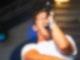 Ein Sänger steht der Kamera zugewandt. Er singt in ein Mikrofon und hat dabei die Augen geschlossen.