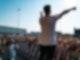 Die Rückenansicht eines Mannes, der auf einer Bühne steht und beide Arme in die Luft gestreckt hat. Vor ihm steht hinter einer Absperrbande eine menschenmenge.