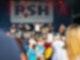 Ein Mann steht zusammen mit einer Band auf einer großen Bühne und streckt die Arme nach oben. Vor der Bühne steht eine Menschenmenge die ihm dabei zusieht.
