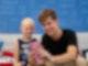Ein junger Mann und ein kleines Mädchen sitzen gemeinsam auf einem Sofa. Der Mann hält ein rosanes Handy in der Hand auf das beide schauen.