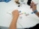 Auf dem Tisch liegt ein weißes TShirt mit der Aufschrift R.SH Kindertag 2019. Davor sitzt eine Person von der nur die Unterarme und Hände sichtbar sind. Die rechte Hand hält einen Edding um auf dem TShirt zu unterschreiben.