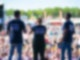 Eine Frau steht gemeinsam mit zwei Männern, die links und rechts neben ihr stehen, auf einer großen Bühne. Die Personen stehen mit dem Rücken zur Kamera auf und blicken auf eine Menschenmenge die vor der Bühne steht.