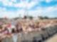 Eine Menschenmenge steht, links im Bild, hinter einer Absperrbande.