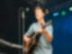 Ein junger Mann steht auf einer Bühne und spielt Gitarre.