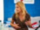 Eine junge Frau mit langen blonden Haaren sitzt der Kamera zugewandt an einem Tisch. Sie schaut nach links und gestikuliert mit den Händen.