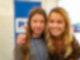 Eine junge Frau mit langen blonden Haaren hat den Arm um die Schulter eines jungen Mädchens gelegt, das rechts neben ihr steht. Beide lächeln in die Kamera.