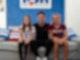 Der Sänger Nico Santos sitzt gemeinsam mit zwei jungen Mädchen auf einer Couch. Die Mädchen sitzen links und rechts von ihm.