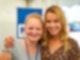 Eine junge Frau mit langen blonden Haaren hat den Arm um die Schulter eines Mädchens gelegt, das rechts neben ihr steht. Beide lächeln in die Kamera.