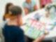 Ein junger Mann, der an einem Tisch sitzt, hält ein Plakat in der Hand auf dem Team Taylor steht. Er sitzt mit dem Rücken zur Kamera, links im Bild.