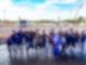 Eine Gruppe von Menschen steht auf einer großen Bühne und jubelt in die Kamera. Im Hintergrund ist eine Menschenmenge zu sehen die auf die Bühne sieht.