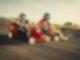 Zwei Kinder fahren in einer roten und einer gelben Seifenkiste eine Straße runter. Sie haben grüne Helme auf und gucken konzentriert auf die Fahrbahn.
