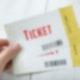 Eine Hand hält zwei Tickets.