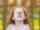 Ein Kind mit roten Haaren steht in der Natur. Es steht der Kamera zugewandt und lacht herzlich. Auf seiner Nase sitzt mit ausgebreiteten Flügeln ein Schmetterling.