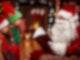Ein kleines Mädchen und ein kleiner Junge stehen vor einem Mann der auf einem Stuhl sitzt, ein Weihnachtskostüm und einen langen weißen Bart sowie eine rot weiße Mütze auf dem Kopf trägt. In seinen Händen hält er ein aufgeklapptes großes Buch.