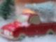 Ein rotes Spielzeugauto mit Ladefläche steht in künstlichem Schnee, vor kleinen künstlichen Miniaturtannen. Auf der Ladefläche liegt eine Miniaturtanne.