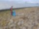 Ein Mann steht auf Steinen vor einem Meer und hat eine Mülltüte in seiner rechten Hand.
