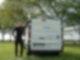 Ein Mann und ein Auto stehen auf einer Rasenfläche. Der Mann lehnt mit seinem linken Arm am Auto und guckt in die Kamera.