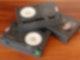 Auf einem Holztisch liegen drei Videokassetten. Die eine Kassette liegt auf den anderen beiden drauf.