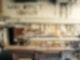 In einem Raum steht ein Holztisch. Am den Wänden hängen viele verschiedene Werkzeuge und Materialien. Darüber hängen selbstgemachte Buchstaben an der Wand, die Werk Statt Konsum darstellen.